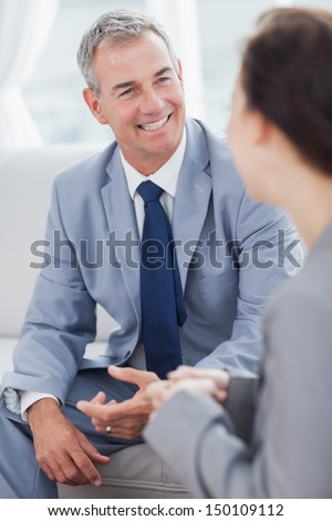 Smiling businessman talking to his workmate in bright office - stock photo