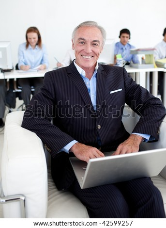 Smiling businessman using a laptop with his team in the background - stock photo