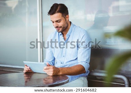 Smiling businessman using a tablet outside the cafe - stock photo