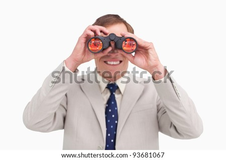 Smiling businessman using binoculars against a white background