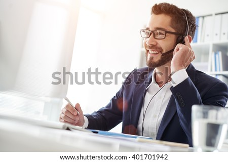 Smiling businessman using headset when talking to customer - stock photo