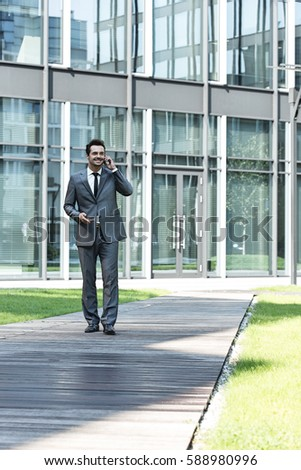 Smiling businessman using mobile phone while walking on path outside office