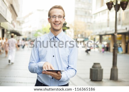 Smiling Businessman Using Tablet Computer in public space and looking on street - stock photo