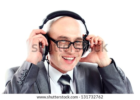 Smiling businessman wearing headphones looking to camera, listening to music