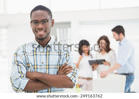 Smiling businessman with arms crossed in front of his colleagues - stock photo