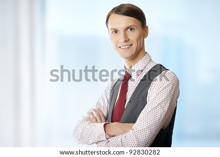 Smiling businessman with arms crossed in his office - stock photo