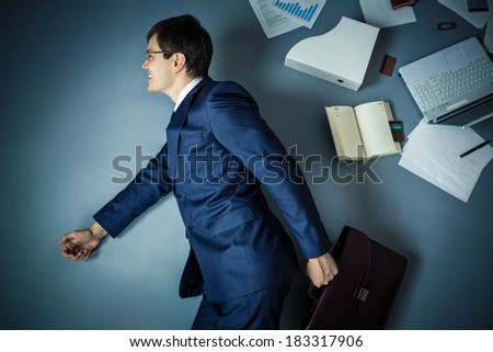 Smiling businessman with briefcase in studio - stock photo