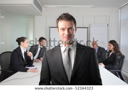 Smiling businessman with group of business people on the background in a meeting room