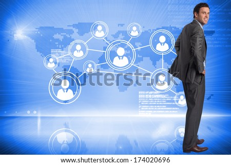 Smiling businessman with hands on hips against futuristic technology interface