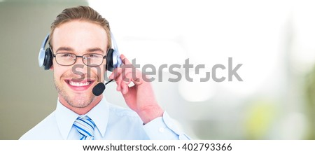Smiling businessman with headset interacting against steaming cup of coffee - stock photo