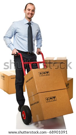 smiling businessman with red handtruck and boxes - stock photo