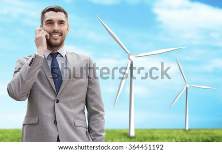 smiling businessman with smartphone outdoors - stock photo