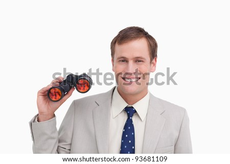 Smiling businessman with spy glasses against a white background - stock photo
