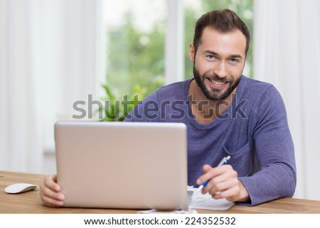 Smiling businessman working on a laptop as he sits at a desk in front of a window in a home office - stock photo