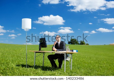 Smiling businessman working with computer and table in green meadow - stock photo