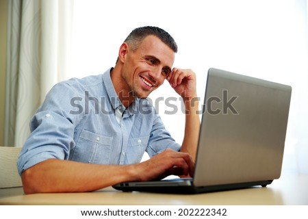Smiling businessman working with laptop - stock photo