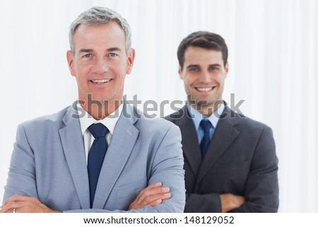 Smiling businessmen posing in bright office looking at camera - stock photo