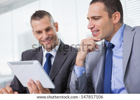 Smiling businessmen working together on their tablet in bright office - stock photo