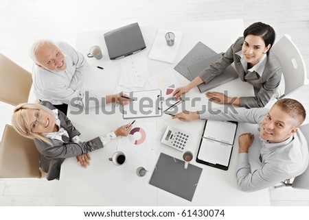 Smiling businesspeople sitting at meeting table, working, pointing at document, smiling at camera, high angle view. - stock photo