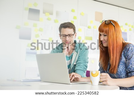 Smiling businesspeople using laptop at desk in creative office - stock photo