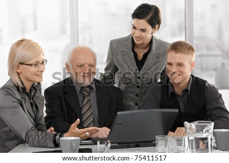 Smiling businessteam on meeting, mid-adult businesswoman showing computer work to coworkers.? - stock photo