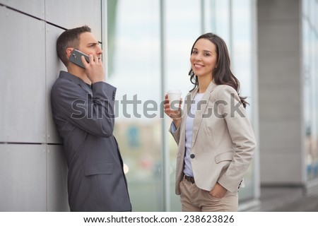 Smiling businesswoman and businessman talking on his mobile phone during coffee break - stock photo