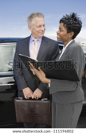 Smiling businesswoman and businessman with folder - stock photo