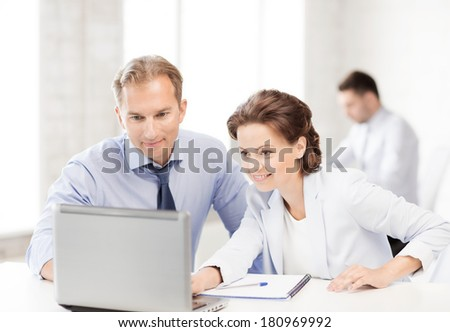 smiling businesswoman and businessman working with laptop in office - stock photo