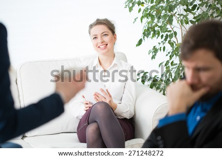 Smiling businesswoman and her colleagues in office - stock photo