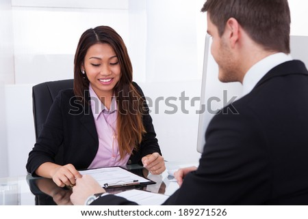Smiling businesswoman discussing over document with male colleague in office - stock photo