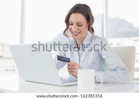 Smiling businesswoman doing online shopping through laptop and credit card in office - stock photo
