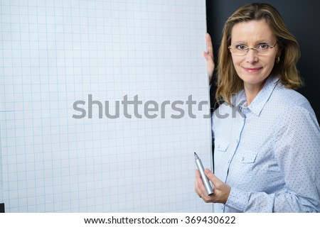Smiling businesswoman giving a presentation or in house training holding a marker in her hand as she stands alongside a flip chart