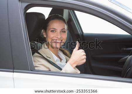 Smiling businesswoman giving thumbs up at new car showroom