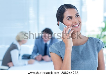 Smiling businesswoman having a phone call in an office - stock photo