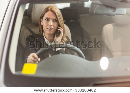 Smiling businesswoman having a phone call while sitting in a car at new car showroom - stock photo