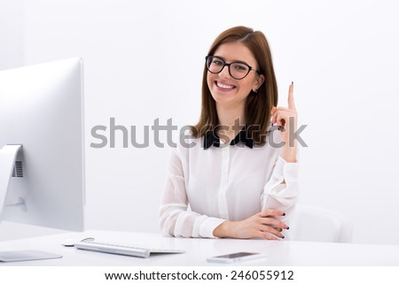 Smiling businesswoman having idea. Pointing finger up - stock photo
