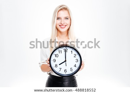 Smiling businesswoman holding big clock isolated on a white background and looking at camera