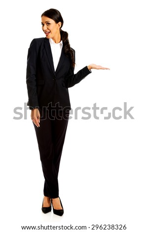 Smiling businesswoman holding copyspace on the left hand. - stock photo