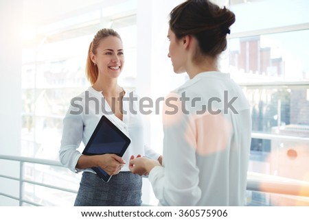Smiling businesswoman holding digital tablet and talking with partner while standing in modern office interior, team of professional employees discussing ideas of project after working on touch pad