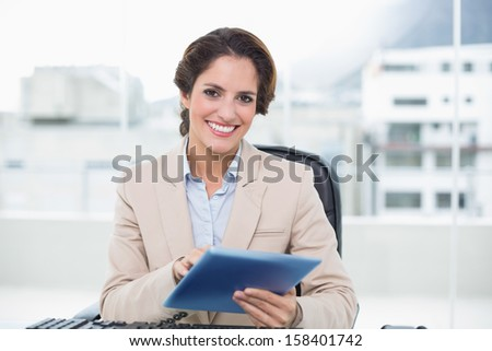 Smiling businesswoman holding tablet in bright office