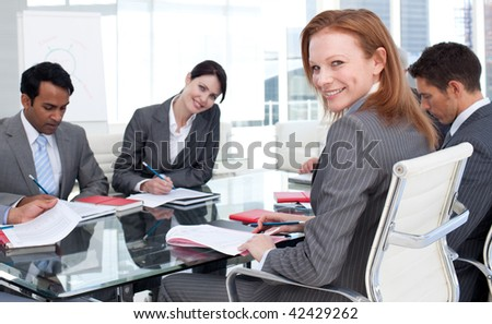 Smiling businesswoman in a meeting with her team in the office