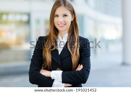 Smiling businesswoman in an urban setting - stock photo