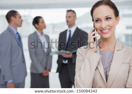 Smiling businesswoman in bright office calling while colleagues talking together