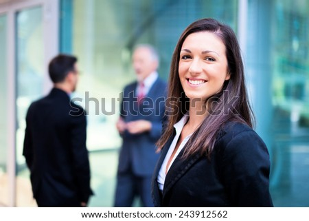 Smiling businesswoman in front of a group of business people