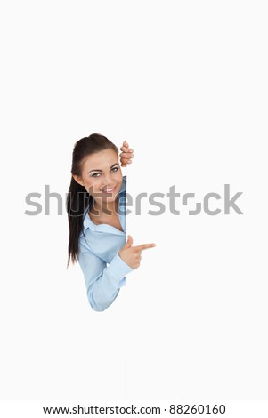 Smiling businesswoman looking around the corner while pointing against a white background - stock photo