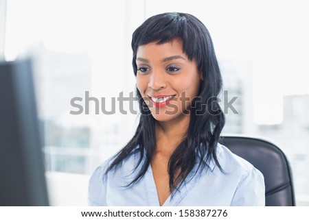 Smiling businesswoman looking at her computer in office - stock photo