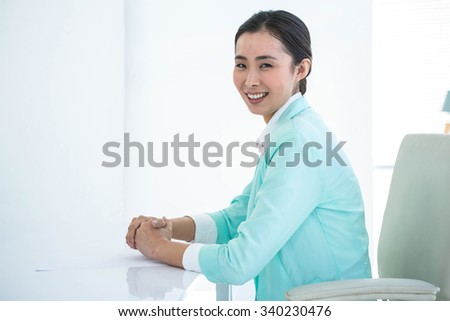 Smiling businesswoman looking at the camera at the desk in work