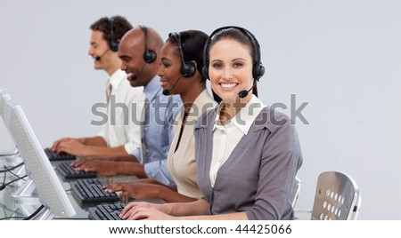 Smiling businesswoman looking at the camera with her team in the background - stock photo