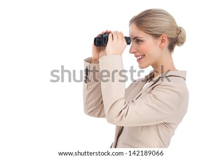Smiling businesswoman looking away with binoculars on a white background