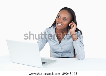 Smiling businesswoman making a phone call while using a laptop against a white background - stock photo